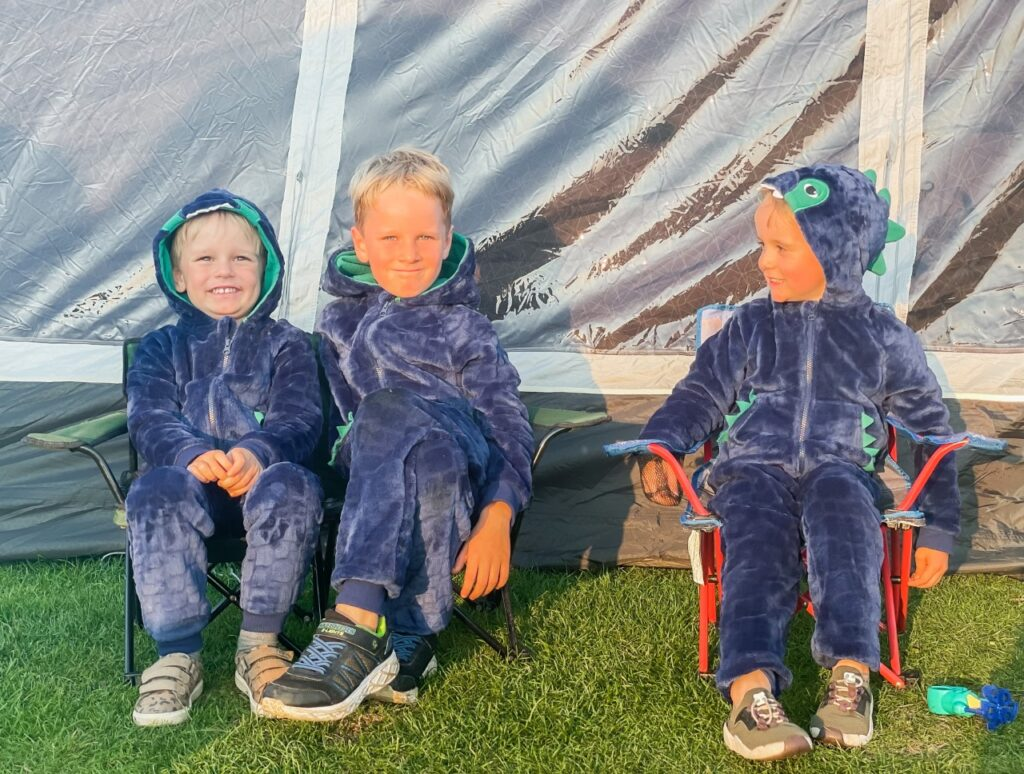 Brothers wearing dinosaur onesies sit outside a tent
