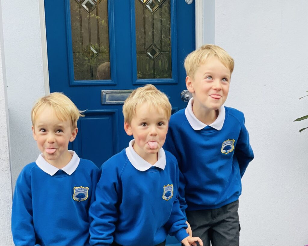 Three boys in uniform on the first day of school when the youngest child is starting school
