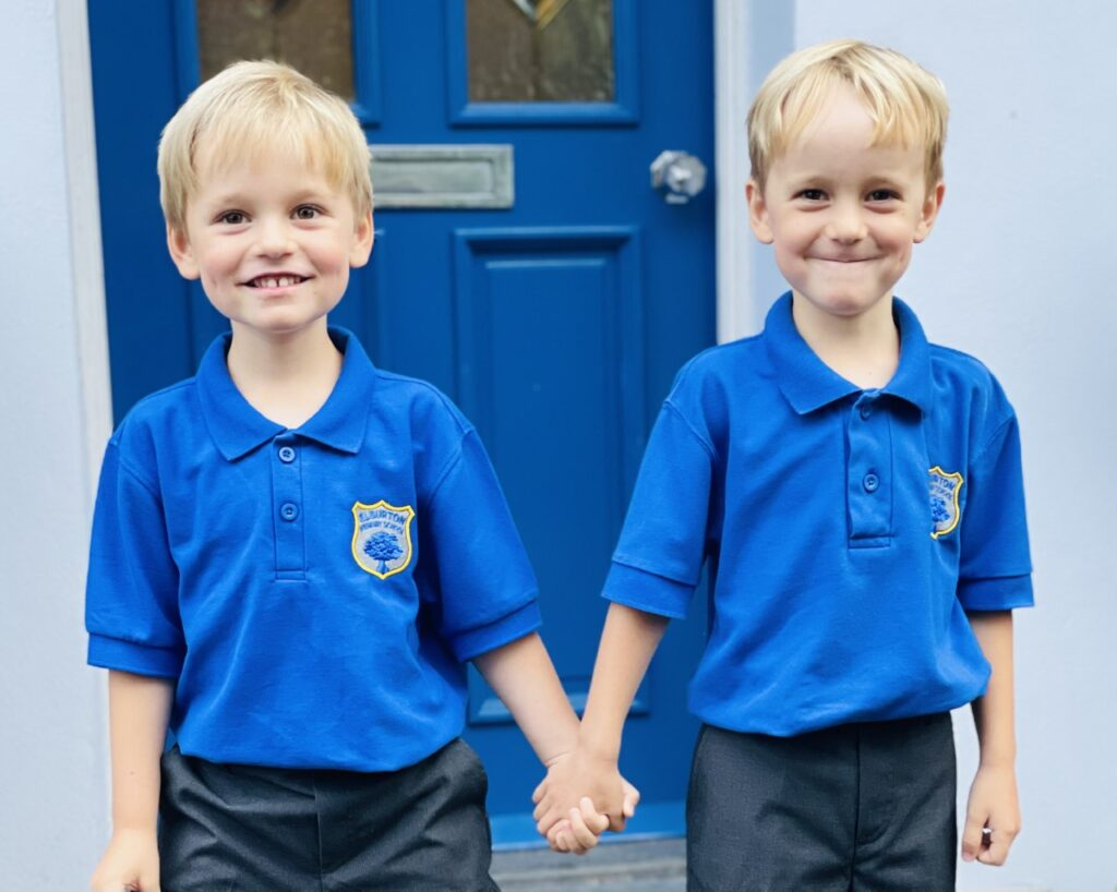 Four year old twin brothers starting school in school uniform on the doorstep
